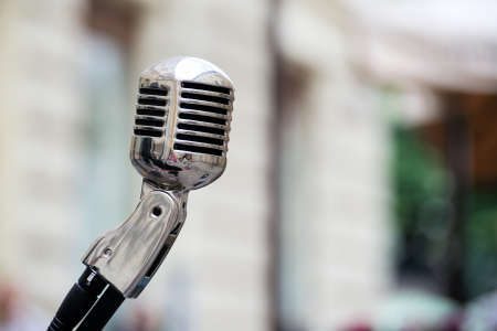 voices: Retro style microphone on stage in the spotlight performance of the musical group.