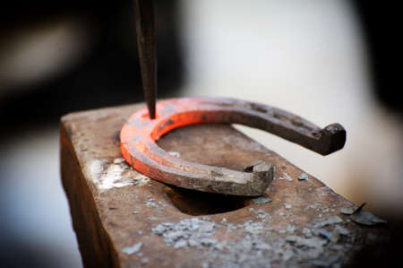 The blacksmith kicks a horseshoe close up .