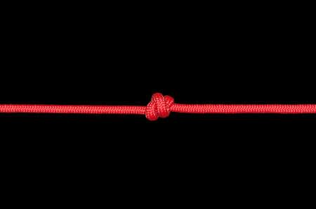 Nodo su una corda su uno sfondo scuro. Archivio Fotografico