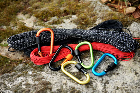 Metal carabine and rope for mountaineering. Photo of colored carabines and rope. Climbing concept Standard-Bild