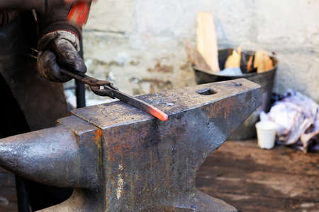 Blacksmith working metal with hammer on the anvil in the forge Stock Photo