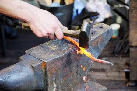 Blacksmith working metal with hammer on the anvil in the forge Stok Fotoğraf