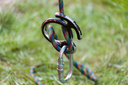 Climbing sports image of a carabiner on a rope . Climbing concept