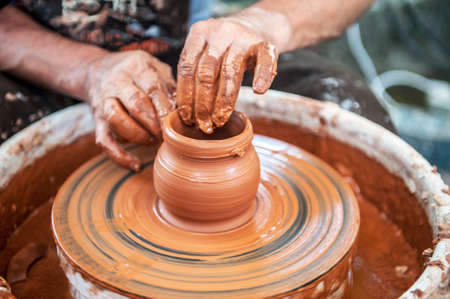 The potter makes pottery dishes on potter's wheel. The sculptor in workshop makes clay product closeup. Hands of the potter. Foto de archivo