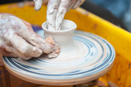 The potter makes pottery dishes on potter's wheel. The sculptor in workshop makes clay product closeup. Hands of the potter. Stock Photo