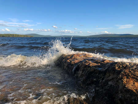 storm waves hitting a rock on a lake in the North of Russia in the country