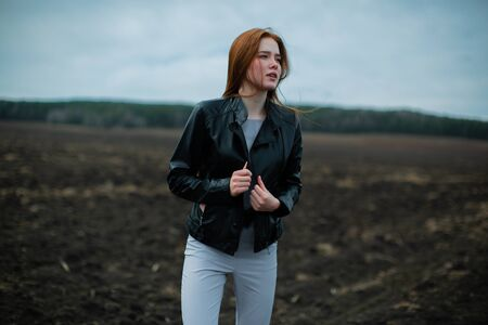 red-haired girl stands in the middle of a field of black earth.