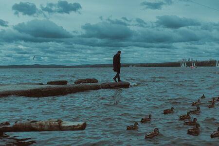 A lone man walks along the stone pier to the water.