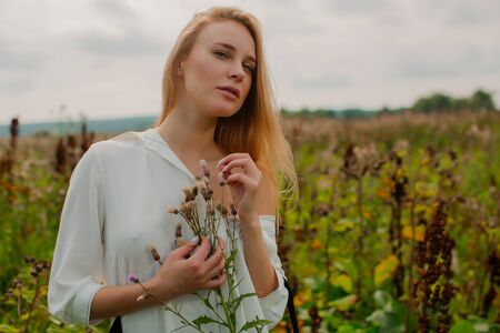 A tender young blonde looks at a cypress flower in her hands. Stock Photo