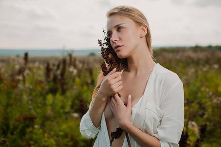 Fille romantique douce tenant un bouquet de fleurs séchées.