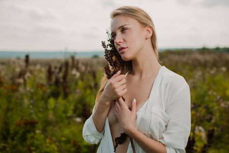 Gentle romantic girl holding a bouquet of dried flowers.