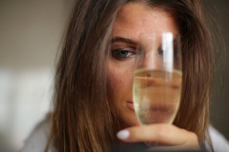 Portrait of an alcoholic woman who hides half of her face with a glass of alcohol.