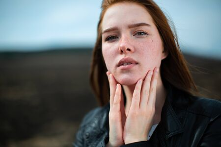 Stylish redhead girl puts her fingers to her face and looks at us.