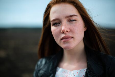 Portrait of a red-haired woman with freckles, illuminated by the sun.