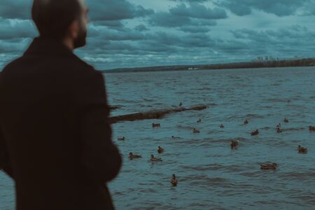 A man stands at the water in which the ducks swim.