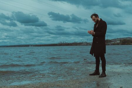 A lone man in black clothes stands thoughtfully on the shore of the pond.