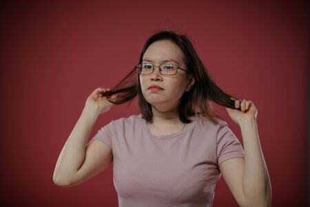 A woman with glasses is holding her hair.