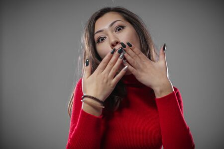 Beauty with a stylish manicure covers her mouth with her hands. Stock Photo - 133847253