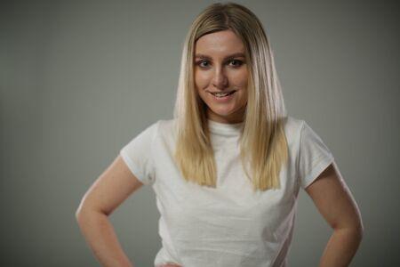A cute blonde in a white t shirt stands