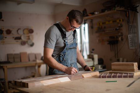 The man-a carpenter takes measurements on the wood. Banque d'images - 134927487