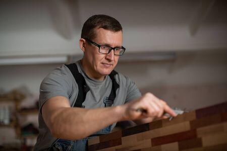 Adult man with glasses handles wood carpentry tool