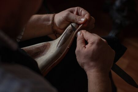 A shoemaker cuts the sole of a Shoe with a shoemakers knife.