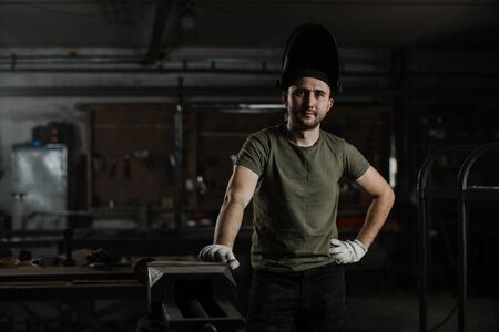 Portrait of a young handsome male welder in a protective mask on his head