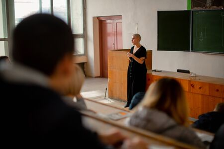 A woman teacher with short hair stands at the lectern and tells a lecture to her students. Stock Photo