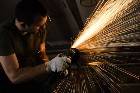 A man works with metal and sparks fly beautifully