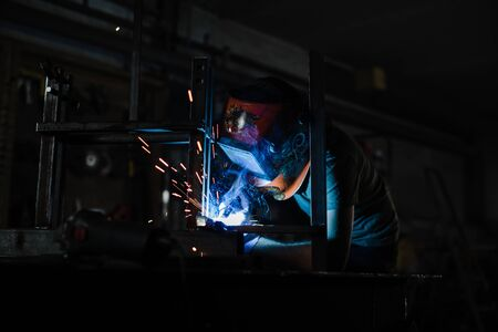 A man in a helmet works with a welding machine and sparks fly in all directions