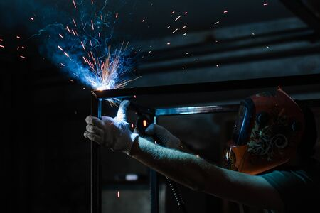 The process of welding a metal structure using a welding machine. Welder in a protective mask at work