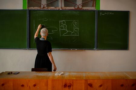 A female teacher stands back and writes with chalk on a chalk green Board