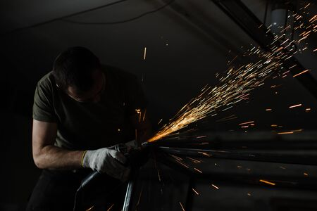 Silhouette of a brutal man engaged in welding. Stock Photo