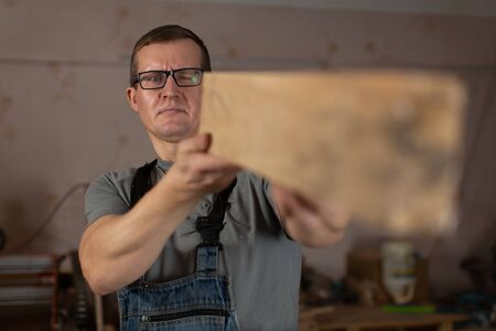 A male carpenter holds a bar of wood at arms length and evaluates his work.