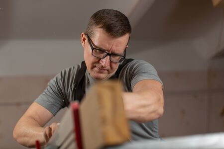 Portrait of a male carpenter at work in a carpenters shop. Stock Photo