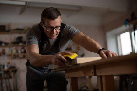 Tischlermeister häutet Holzwerkstück.