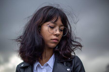 Asiatisches Schulmädchen mit Brille, die gedankenverloren aussieht. Standard-Bild