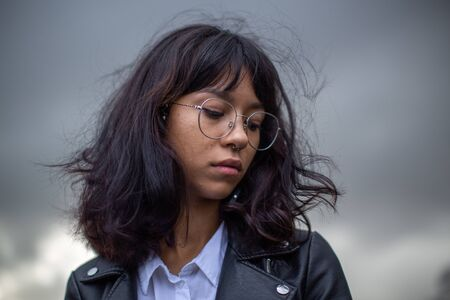 Aziatisch schoolmeisje met een bril die in gedachten verzonken over iets kijkt. Stockfoto
