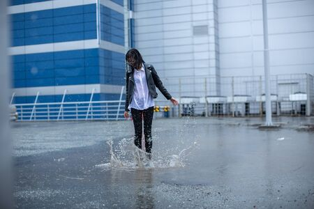 The girl jumps on a huge puddle.