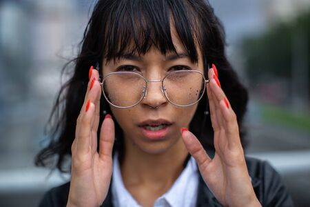 Soaked in the rain, the Asian woman holds her glasses with her hands with a red manicure.