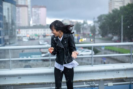 A thin girl in black dodges the gusts of wind and rain.