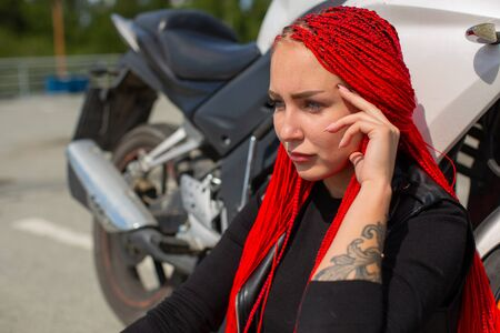 Cool beauty with red hair was thinking near the motorcycle. Stock Photo - 134614075