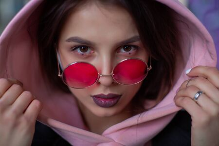 Beauty in crimson glasses looks at you from the hood of a powdery hoodie Stock Photo - 134614142