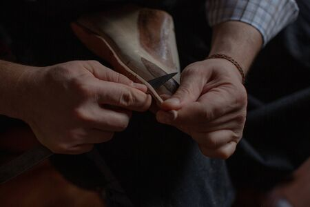 The hands of the shoemaker at work make the sole for new handmade shoes. Stock Photo - 134614259
