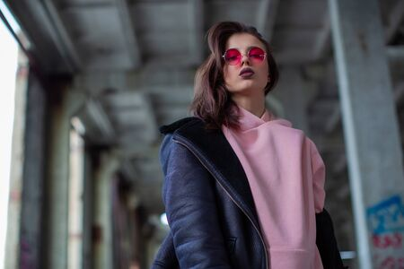 Bold fashionable girl in a crimson colored glasses and wide open jacket Stock Photo