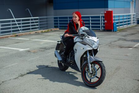 Sexy girl with red hair on white motobike Stock Photo
