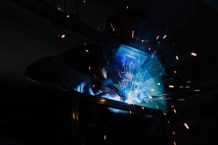 Portrait of a welder at work with a welding machine.