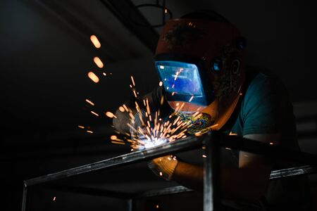 The welder works with a welding arc over a metal structure