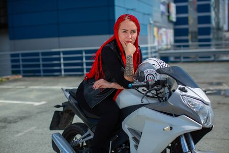 Beauty with red hair sitting on a motorcycle in a thoughtful pose