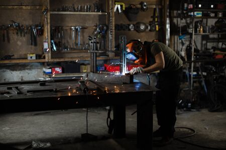 A male welder in a protective helmet works in his workshop.
